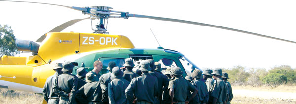 Ranger trainees gather around a patrol helicopter for instruction.